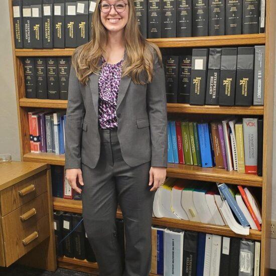 Paige Ricks in front of bookshelf full of books